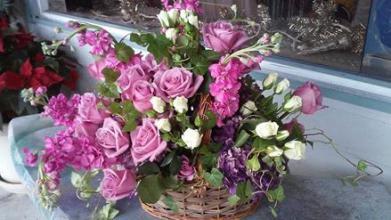 Purple& white roses in a wicker basket